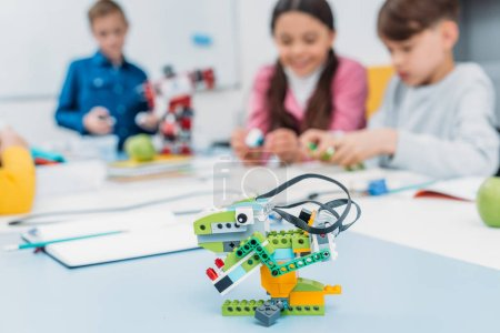 multicolored handmade robot at desk with schoolchildren at background in stem class