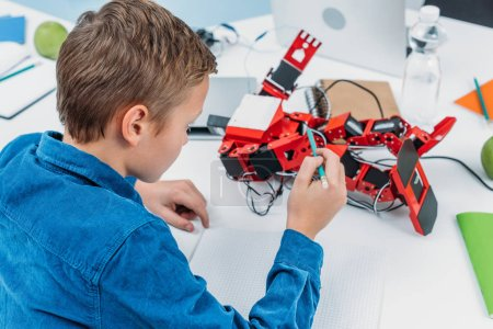 schoolboy sitting at desk and touching with pencil red handmade robot during stem lesson