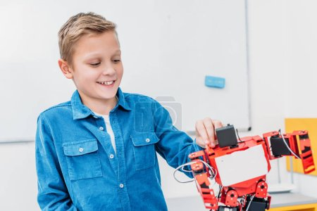 smiling schoolboy touching red robot in stem class