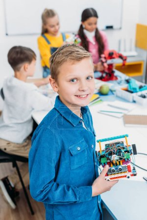 smiling schoolboy holding robot and looking at camera with classmates at background in classroom