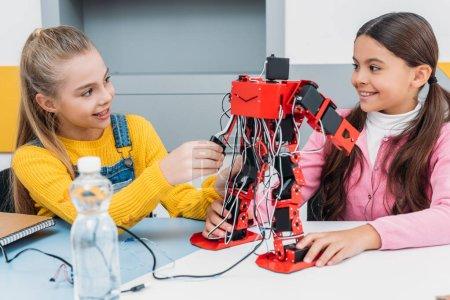 smiling schoolgirls constructing red robot in science class