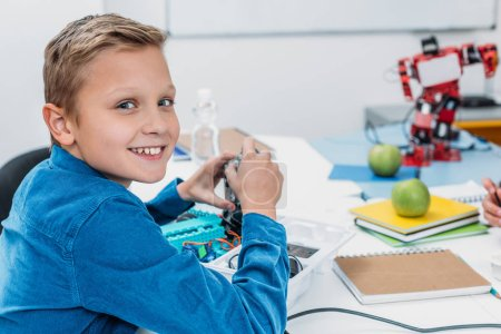 schoolboy sitting at desk and looking at camera in stem education class