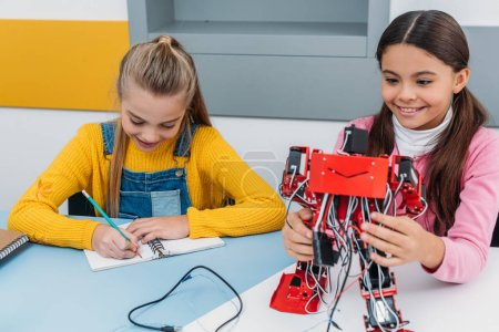 smiling schoolgirls writing in notebook and holding red robot at desk in stem education class