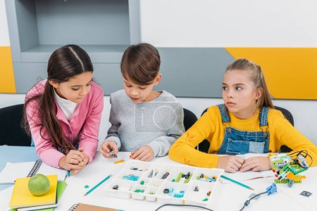 Photo for Concentrated schoolchildren constructing robot with details during STEM lesson - Royalty Free Image
