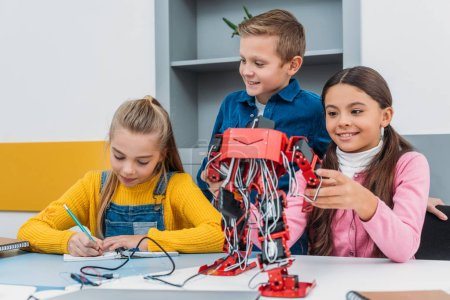 smiling schoolchildren making red robot in stem education class