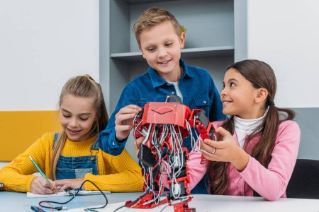 smiling schoolchildren making electric robot in stem class