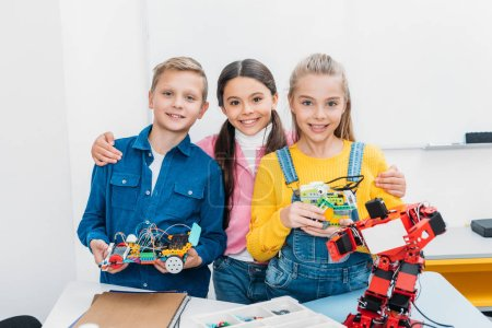 happy schoolchildren looking at camera and holding mechanical robots in stem class