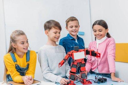 smiling schoolchildren looking at red robot handmade on desk in stem class