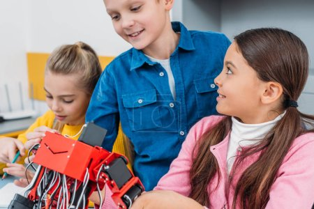 close up view of schoolchildren with handmade electric robot in stem class