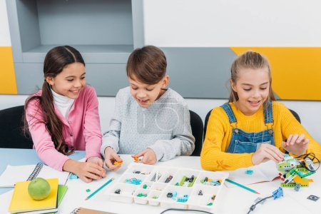 Photo for Happy children sitting at desk and constructing robot in stem education class - Royalty Free Image