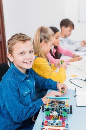 preteen children sitting at desk in stem education class