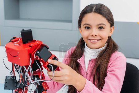 close up view of schoolgirl smiling, holding red handmade robot and looking at camera in stem class