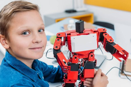 smiling schoolboy holding red robot and looking at camera in stem class