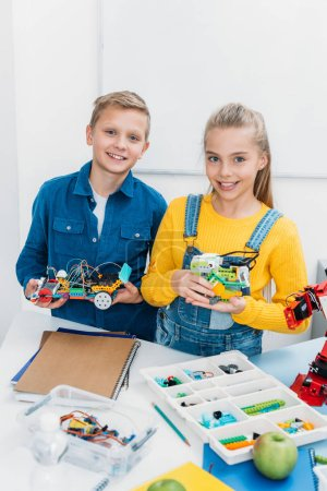 smiling children holding electric robots in stem education class