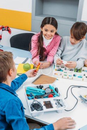 preteen schoolchildren making robot with details in stem education class