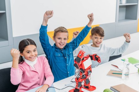 children joying and raising hands at desk with electric robot during stem lesson