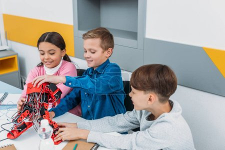 smiling schoolchildren touching red electric robot on desk in stem class