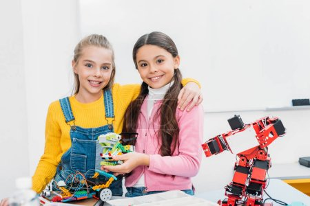 smiling schoolgirls holding robot and looking at camera in stem class