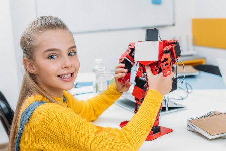 smiling schoolgirl holding red electric robot and looking at camera in stem education class