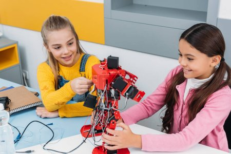 smiling schoolgirls touching red handmade robot in stem class