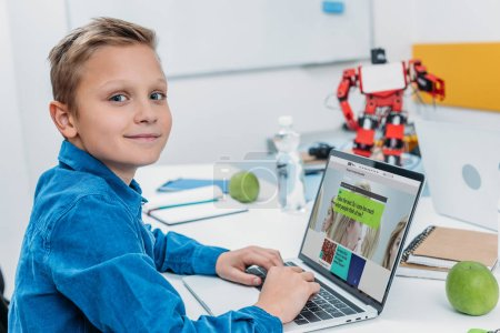 smiling boy using laptop with science website on screen and taking psychological test