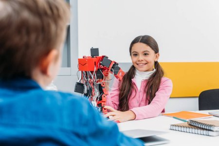 adorable schoolgirl and schoolboy sitting at desk and working together on robot model at STEM class