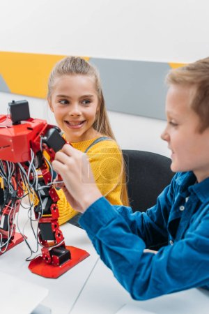 smiling schoolchildren programming robot together during STEM educational class