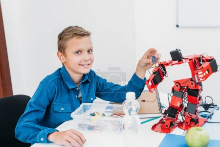 Photo for Schoolboy sitting at table with robot model at STEM classroom and looking at camera - Royalty Free Image