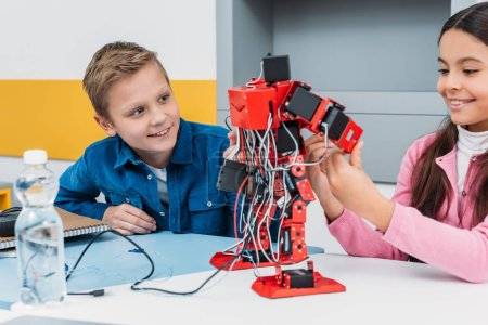 adorable schoolgirl and smiling schoolboy sitting at desk and working together on robot model at STEM class