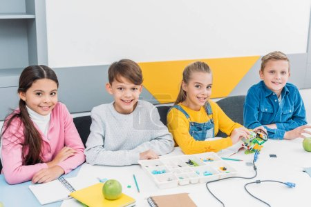 happy classmates at desk looking at camera and working in STEM classroom
