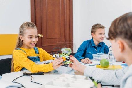 Photo pour Écolier donnant écolière robot modèle à la leçon de programmation STIM - image libre de droit