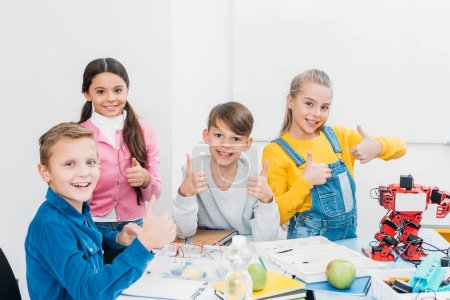 cheerful schoolchildren looking at camera and showing thumbs up while having STEM lesson