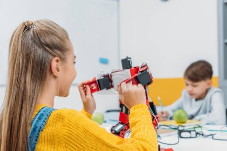 schoolgirl sitting at table and holding robot model during STEM lesson with classmate on background
