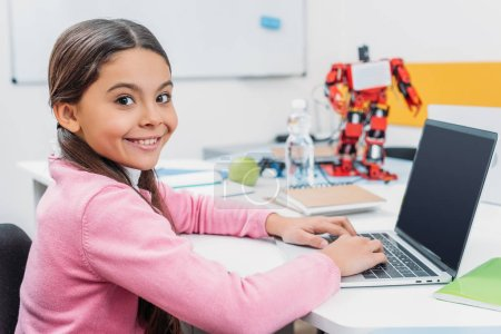 adorable schoolgirl sitting at table with robot model, looking at camera and using laptop with blank screen during STEM lesson