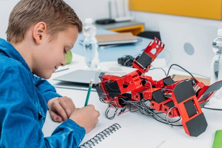 schoolboy sitting at desk with robot model and writing in notebook during STEM lesson