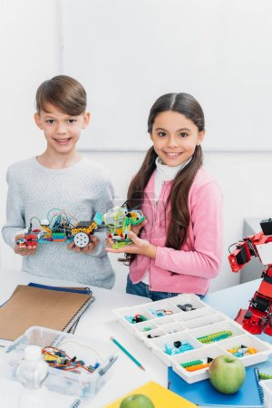 happy kids looking at camera and presenting robot models at STEM lesson
