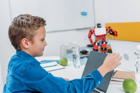 schoolboy sitting at table with robot model and using laptop during STEM lesson