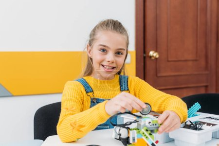 cheerful schoolgirl looking at camera and working on handmade robot model during STEM lesson
