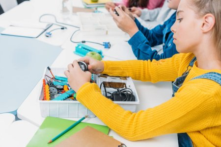schoolgirl sitting at table and working together with classmates on STEM project in classrom
