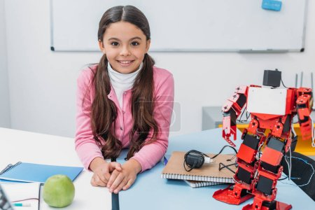 adorable smiling schoolgirl sitting at table with robot model and looking at camera at STEM classroom