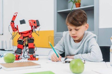 Photo pour Écolier concentré assis au bureau avec modèle de robot et écrit dans un cahier pendant la leçon de STIM - image libre de droit
