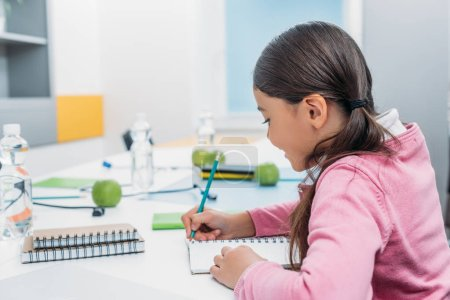 schoolgirl writing in notebook during lesson in classroom