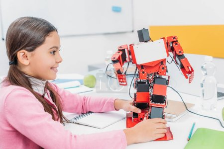 adorable schoolgirl sitting at table in STEM classroom and playing with robot model