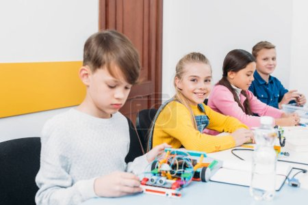 adorable schoolgirl looking at camera while classmates working at desk during STEM programming lesson