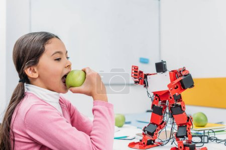 schoolgirl eating apple and sitting at table with robot model at STEM classroom