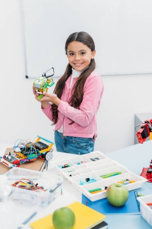 adorable schoolgirl looking at camera and presenting handmade robot model at STEM lesson
