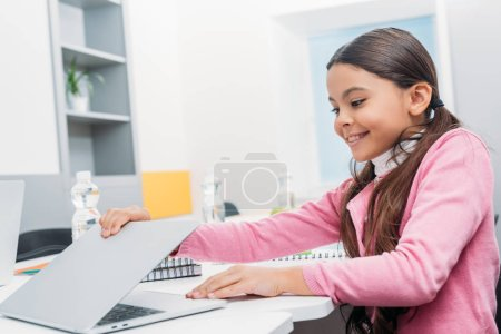 Photo for Smiling schoolgirl sitting at desk and opening laptop during lesson in classroom - Royalty Free Image