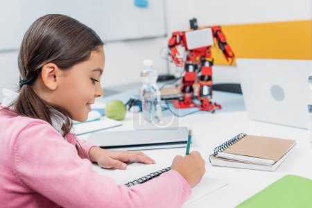 schoolgirl sitting at desk with robot model and writing in notebook during STEM lesson