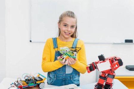 Photo for Happy schoolgirl looking at camera and presenting handmade robot model at STEM lesson - Royalty Free Image