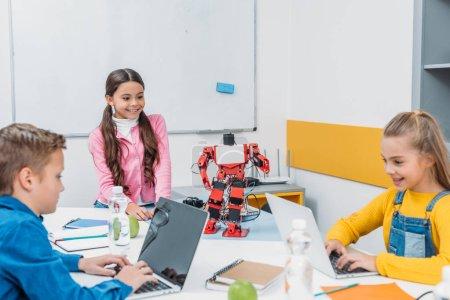 Photo pour Souriant écoliers programmation robot ensemble et en utilisant des ordinateurs portables pendant la classe éducative STIM - image libre de droit